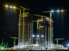 An image of the 3 towers of Azuri Peninsula under construction at night.